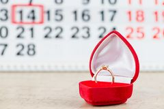 Concept Valentine`s Day, gold ring, heart and pastries on backgr. Ound on the calendar for February 14 Stock Image