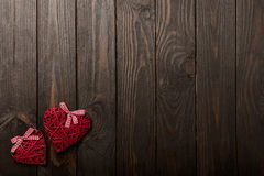 Concept of Valentine`s Day. Wicker hearts on dark wooden backgro stock images