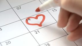 Writing Red Heart on 14th February on calendar with a red marker. The concept of Valentine`s day stock video footage
