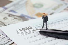 Concept van de belastingsberekening, miniatuur en dun zakenman die het bevinden zich royalty-vrije stock afbeelding