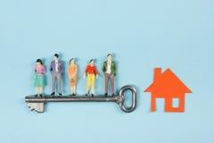 Concept 6 van onroerende goederen De bouwbouw Mensenstuk speelgoed cijfers, document modelhuis met sleutel op de blauwe lijst van Royalty-vrije Stock Foto's