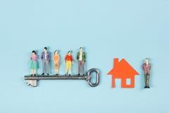 Concept 6 van onroerende goederen De bouwbouw Mensenstuk speelgoed cijfers, document modelhuis met sleutel op de blauwe lijst van Royalty-vrije Stock Afbeeldingen