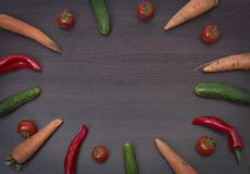 Concept of vegetables on a wooden brown background. Green cucumber and tomatoes on a wooden table. Carrot and paprika with greens Stock Photography