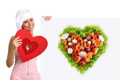 Concept vegetarian diet chef woman pointing billboard salad heart shape. On white background Royalty Free Stock Photos