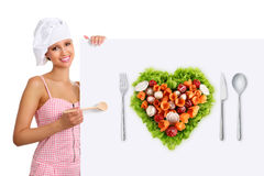 Concept vegetarian diet chef woman pointing billboard salad heart shape stock images