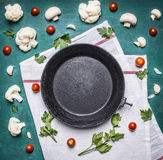 Concept vegetarian food Cauliflower parsley cherry tomatoes old cast iron skillet white napkin rustic wooden background close u Royalty Free Stock Photography