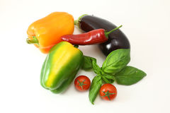 Concept of vegetarian food with tomatoes, yellow paprika, red chilli and green basil Royalty Free Stock Images