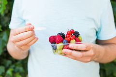 Concept of vegetarians, raw food and diets - close-up of man hold fruits and berries.  royalty free stock image