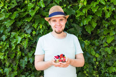 Concept of vegetarians, raw food and diets - Handsome man hold fruits and berries. Concept of vegetarians, raw food and diets - close-up of man hold fruits and royalty free stock photo