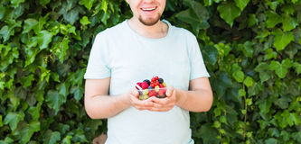Concept of vegetarians, raw food and diets - Handsome man hold fruits and berries. Concept of vegetarians, raw food and diets - close-up of man hold fruits and royalty free stock photography