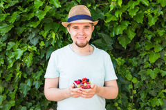 Concept of vegetarians, raw food and diets - Handsome man hold fruits and berries. Concept of vegetarians, raw food and diets - close-up of man hold fruits and royalty free stock images