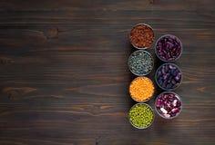 Concept vegetarisch voedsel Graangewassen en peulvruchten in koppen voor het koken op een donkere houten achtergrond Hoogste meni Stock Afbeeldingen