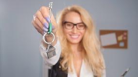 Concept verkoop en huur van onroerende goederen De makelaar in onroerend goed geeft de sleutels aan een flat aan cliënten stock footage