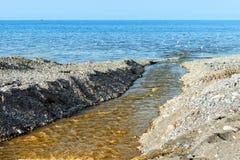 Concept verontreiniging van de wereld` s oceanen en het milieu - de stroom van afvalwater stroomt in het overzees stock afbeelding
