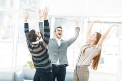 Concept of victory - the jubilant business team standing in a circle, hands up in rejoice success. Royalty Free Stock Photography