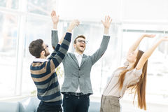 Concept of victory - the jubilant business team standing in a circle, hands up in rejoice success. Royalty Free Stock Photos