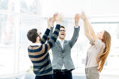 Concept of victory - the jubilant business team standing in a circle, hands up in rejoice success. Royalty Free Stock Images