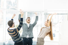 Concept of victory - the jubilant business team standing in a circle, hands up in rejoice success. Stock Photography