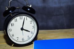 Concept vintage background black retro alarm clock on 16.00 pm or 04.00 am and blue book. N royalty free stock images