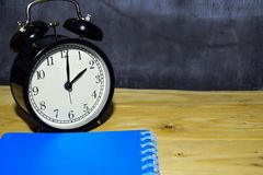 Concept vintage background black retro alarm clock on 14.00 pm or 02.00 am and blue book stock photo