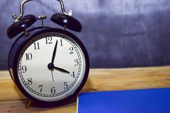 Concept vintage background black retro alarm clock on 16.00 pm or 04.00 am and blue book royalty free stock photos