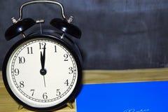 Concept vintage background black retro alarm clock on 12.00 pm or 24.00 am royalty free stock image
