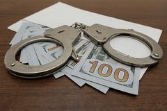 The handcuffs lie on an envelope in which are many hundred dollar bills. Brown wooden background. Concept violation of the law, co stock image