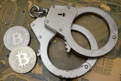 The concept of a violation of the law, cybercrime, financial fraud. Two coins of bitcoin and handcuffs lie on the background of an stock photos