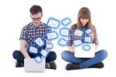 Concept virtuel d'amour - adolescent et fille s'asseyant avec des ordinateurs portables Image stock