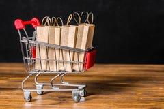 Concept vrijdagverkoop met het winkelen karretje, document zakken op hout Royalty-vrije Stock Foto