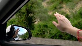 Concept vrijheid, autotravel en avontuur Een vrouwenbestuurder voelt de wind door haar handen terwijl het drijven langs een weg stock video