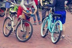 Concept: vrouwen op fietsen De vrouw in heldere kleren houdt de sturen stock foto's