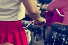 Concept: vrouwen op fietsen De vrouw in heldere kleren houdt de sturen Een deel van het beeld stock afbeelding