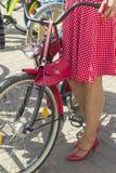 Concept: vrouwen op fietsen Handen die de sturen houden Het meisje draagt een rode stiprok stock foto's