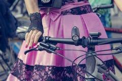 Concept: vrouwen op fietsen Handen die de sturen houden Roze rok met zwart kant royalty-vrije stock afbeelding