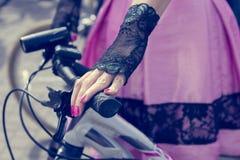 Concept: vrouwen op fietsen Handen die de sturen houden Roze rok met zwart kant stock afbeelding