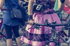 Concept: vrouwen op fietsen Handen die de sturen houden Roze rok met zwart kant royalty-vrije stock foto