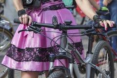 Concept: vrouwen op fietsen Handen die de sturen houden Roze rok met zwart kant royalty-vrije stock fotografie