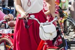 Concept: vrouwen op fietsen Handen die de sturen houden In zijn rechtse zonnebril Witte zak op het stuurwiel royalty-vrije stock afbeelding
