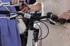 Concept: vrouwen op fietsen Handen die de sturen, in de rechtse telefoon, in de linkerzonnebril houden Een deel van het beeld royalty-vrije stock foto's