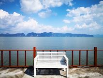 The concept of waiting for hope. The white wooden bench is locat. Ed on the balcony.The backdrop of  the foggy island and the sky is full of clouds. Selective Royalty Free Stock Image