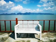 The concept of waiting for hope. The white wooden bench is locat. Ed on the balcony.The backdrop of  the foggy island and the sky is full of clouds. Selective Royalty Free Stock Images