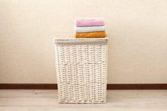 Concept wasserijproces Rieten wasmand met kleurrijke handdoeken stock foto
