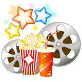 Concept of watching movie. Two film reels and popcorn and glass with drink Stock Photos