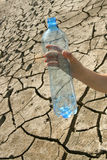 Concept of of water shortage. A hand with an empty bottle on the background of dried ground Royalty Free Stock Images