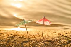 The concept of wedding at sea. Miniature cocktail umbrellas and wedding rings on the beach. At sunset royalty free stock photos