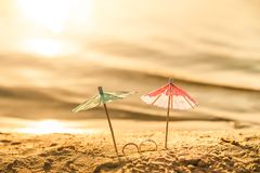 The concept of wedding at sea. Miniature cocktail umbrellas and wedding rings on the beach. At sunset stock photos