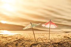 The concept of wedding at sea. Miniature cocktail umbrellas and wedding rings on the beach. At sunset stock image