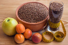 Concept - weight loss. Buckwheat in a ceramic pot, measuring tap Stock Photo