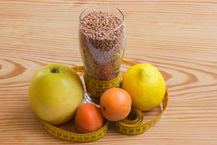 Concept - weight loss. Buckwheat, measuring tape and colorful fr Royalty Free Stock Photography